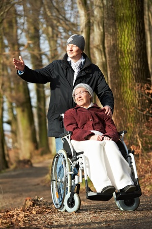 retirees: elderly woman in wheelchair walking with son Stock Photo