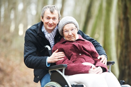 old senior woman in wheelchair with careful son photo