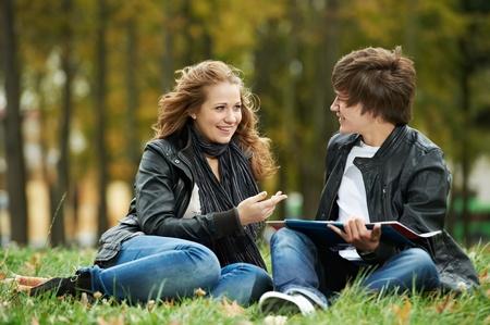 amigas conversando: Dos sonrientes jóvenes estudiantes al aire libre