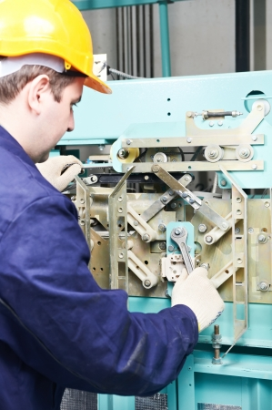 machinist with spanner adjusting lift mechanism  photo