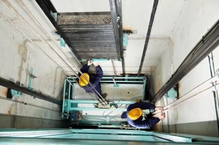 service lift: machinists adjusting lift in elevator hoistway Stock Photo