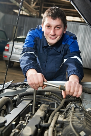 happy automotive mechanic at work with wrench photo