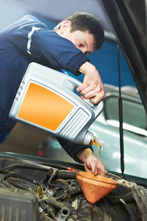 car mechanic pouring oil into motor engine photo