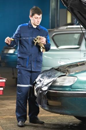 car mechanic inspecting engine oil level photo