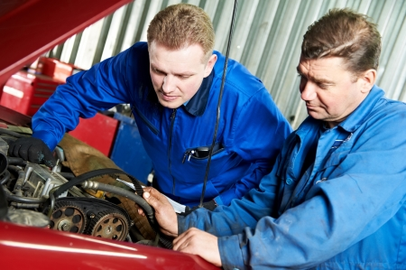 two car mechanic diagnosing auto engine problem photo