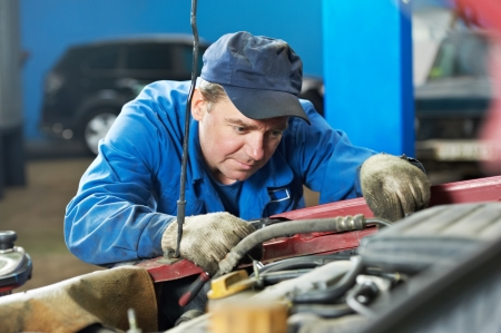 scheduled replacement: car mechanic diagnosing auto engine problem