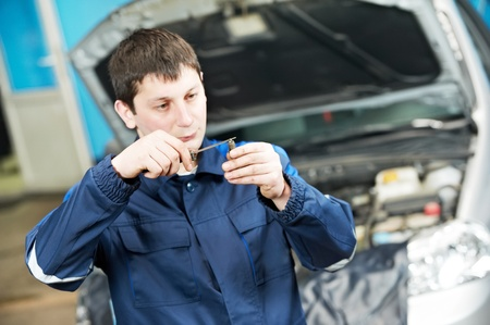 sparking plug: car mechanic inspecting engine sparking plug