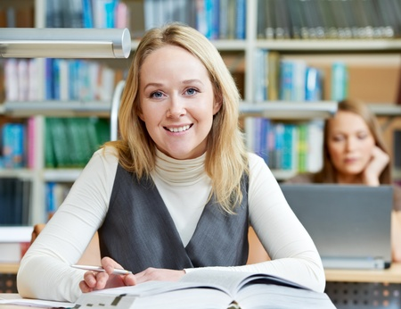 Smiling young adult woman reading  book in library Stock Photo - 13094792