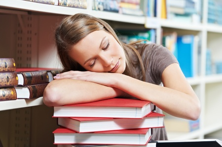 tired young woman sleeping on book in library photo
