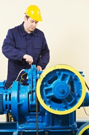 service lift: Machinist tuning elevator brakes mechanism Stock Photo