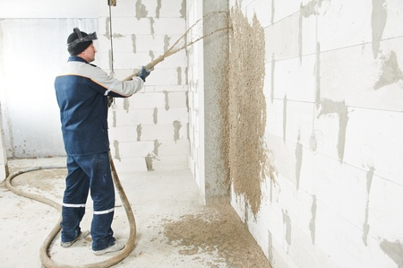plastering: Plasterer at stucco work with liquid plaster Stock Photo