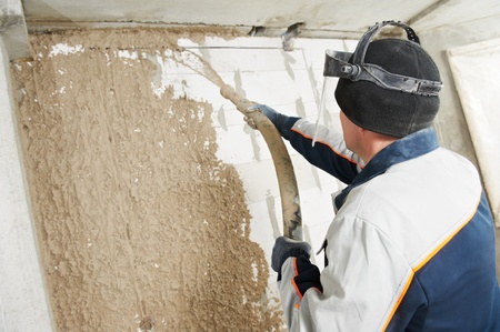 Plasterer at stucco work with liquid plaster photo