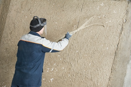 parget: Plasterer at stucco work with liquid plaster Stock Photo
