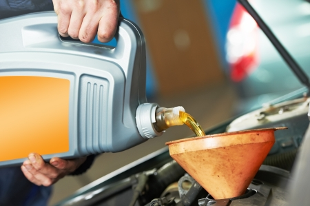 Closeup mechanic hand pouring oil into car motor photo