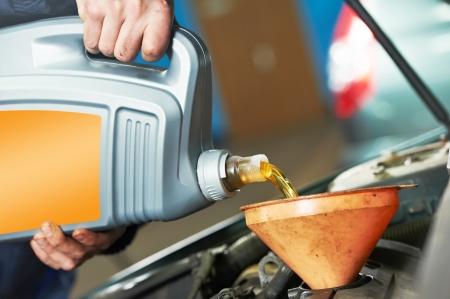 garage automobile: La main de m�canicien Closeup versant de l'huile dans la voiture � moteur