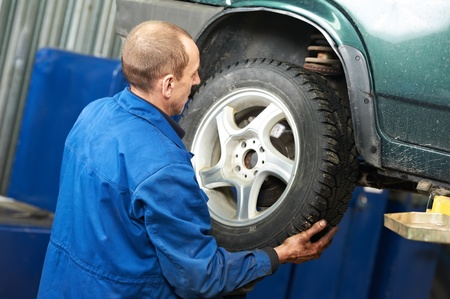 tire service: mechanic installing car wheel at service station