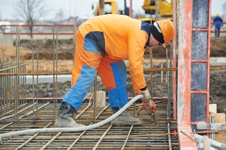 vibration machine: builder worker pouring concrete into form