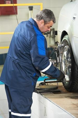alineaci�n: mec�nico auto en el trabajo de alineaci�n de ruedas