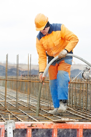 builder worker pouring concrete into form photo