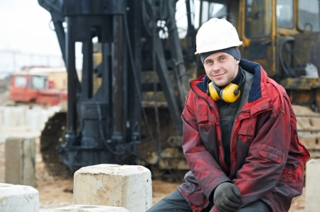 construction project: builder in dirty workwear at construction site Stock Photo