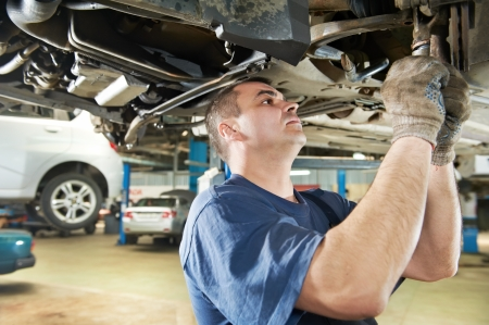 service car: auto mechanic at car suspension repair work