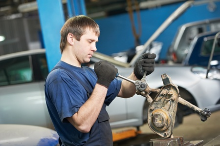 disassembly: auto mechanic at work with wrench spanner