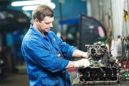 scheduled replacement: auto mechanic at repair work with engine