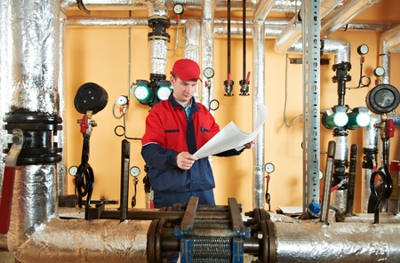 and heating: heating engineer repairman in boiler room Stock Photo