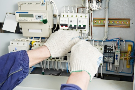 cabling: Electrician tighten the screws with spanner Stock Photo