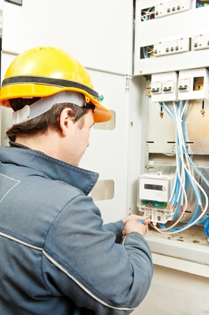 Electrician installing energy saving meter photo