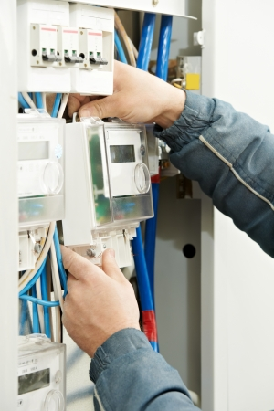Close-up Electrician hands installing energy meter photo