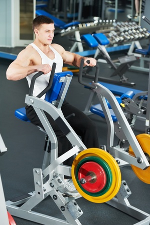 bodybuilder man doing exercises in fitness club photo