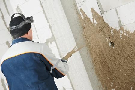 plasterer: Plasterer at stucco work with liquid plaster Stock Photo