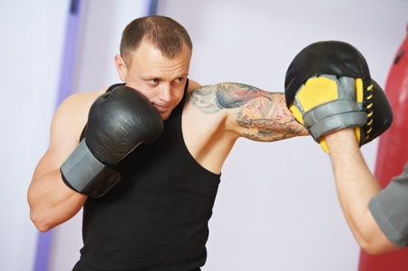 mitts: boxer man at boxing training with punch mitts