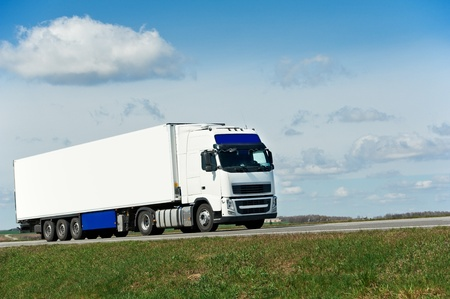 White lorry with white trailer over blue sky photo