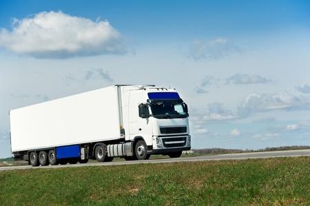 Camion blanc avec remorque blanche sur ciel bleu