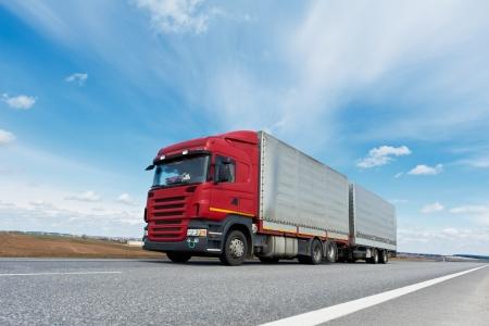 Red camión con remolque gris sobre el cielo azul