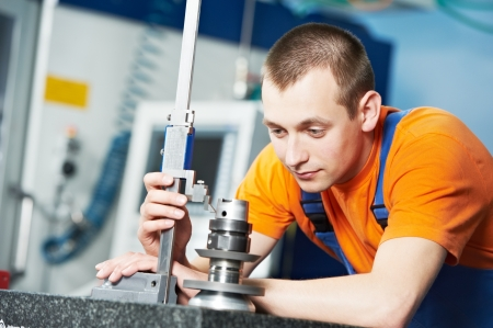 production engineer: worker measuring cutting tool Stock Photo