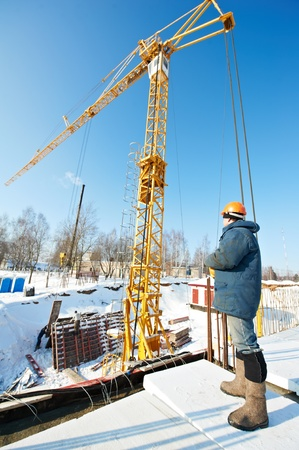 skilled operator: worker with tower crane remote control equipment