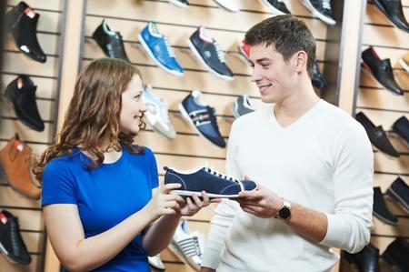 tienda de zapatos: el hombre y la asistente en las compras del zapato
