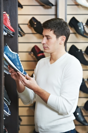 Young man at choosing shoe in clothes store photo