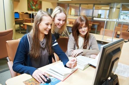 educadores: chicas estudiantes de trabajo con la computadora en la biblioteca Foto de archivo