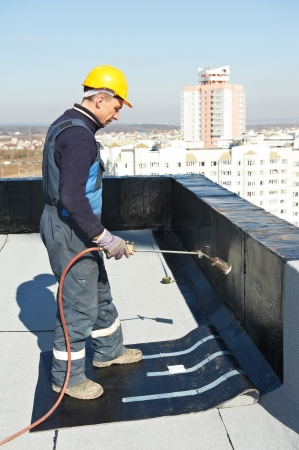Flat roof covering works with roofing felt photo