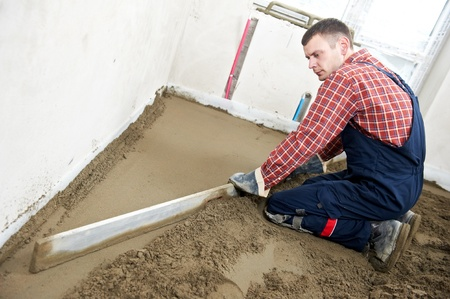 Plasterer concrete worker at floor work Stock Photo - 13425902