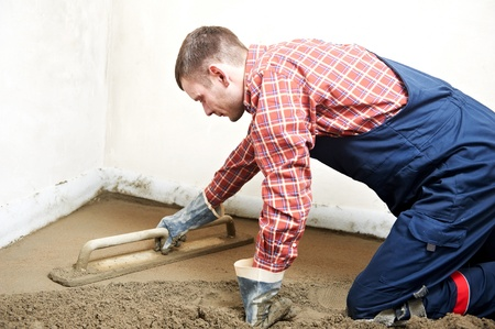 floor covering: Plasterer concrete worker at floor work Stock Photo