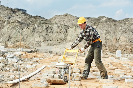 compacting: concrete worker work with pla compactor