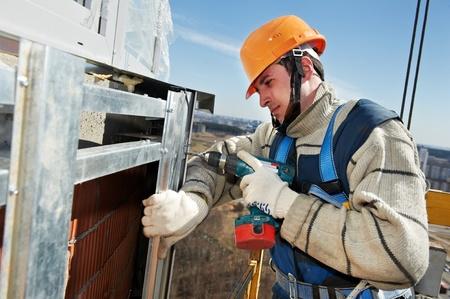 cladding tile: Worker builders at facade tile installation