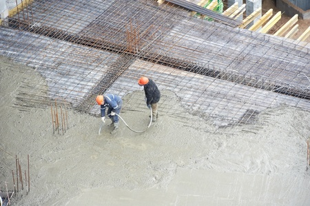 compacting: builder workers at concrete pouring work