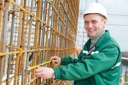reinforcing bar: builder with measure tape Stock Photo