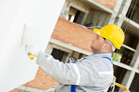 plastering: builder facade painter at work Stock Photo